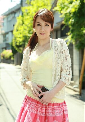 Asiatic beauty with red hair seductively walks on sunny street of huge city