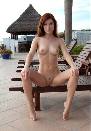 Auburn-haired performer with sexy phenomenal face on sun-lounger at the poolside