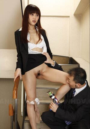 Guy in a suit takes off Asian's nylons on the stairs and aims strange dildo at it