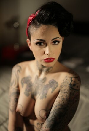 Inked brunette has quite enough talent to pose nude in image of pinup model