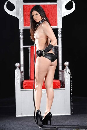 BDSM posing of aroused woman with tiny boobs who holds a stick in her hands